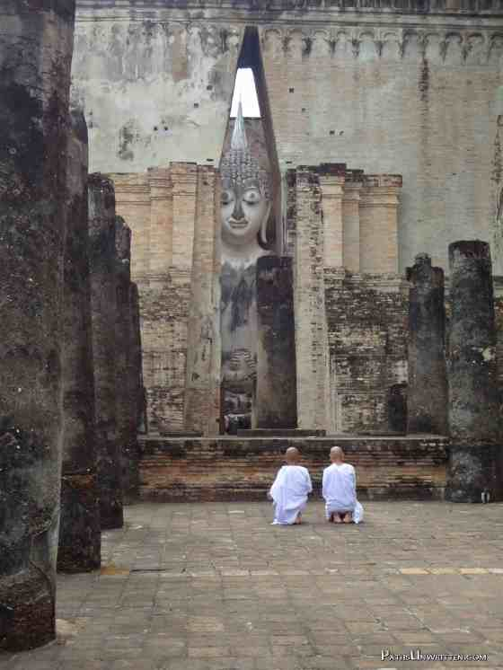 Two nuns ignoring all the tourists around this temple and praying.