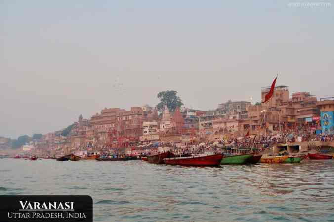 The colorful ghats of Varanasi from the Ganges River at sundown.