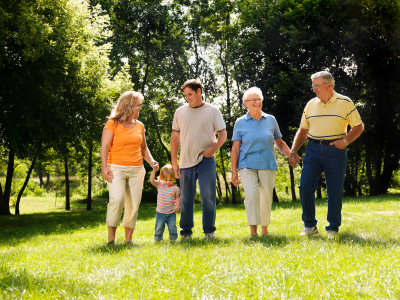 parents with a toddler along with grandparents standing in a field with trees in the background on a sunny day
