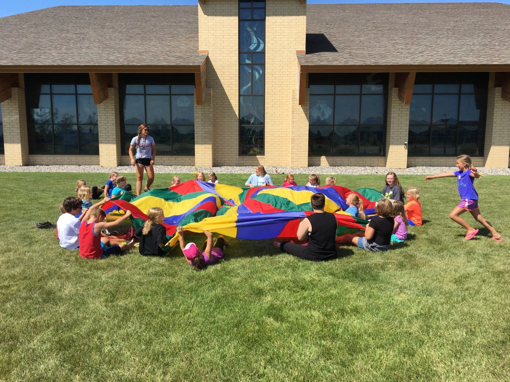 Congregation's kids playing with a colorful parachute.