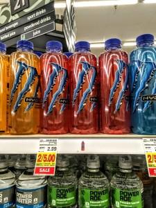 Bottles of Monster Manic Mellon Energy Drink on a store shelf.