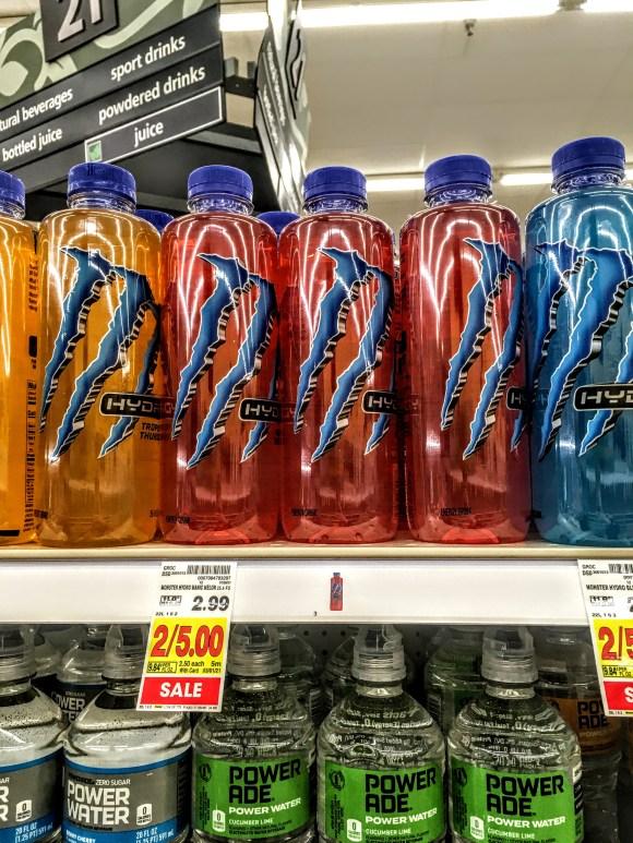 A store shelf displaying bottles of Monster Manic Mellon drinks.