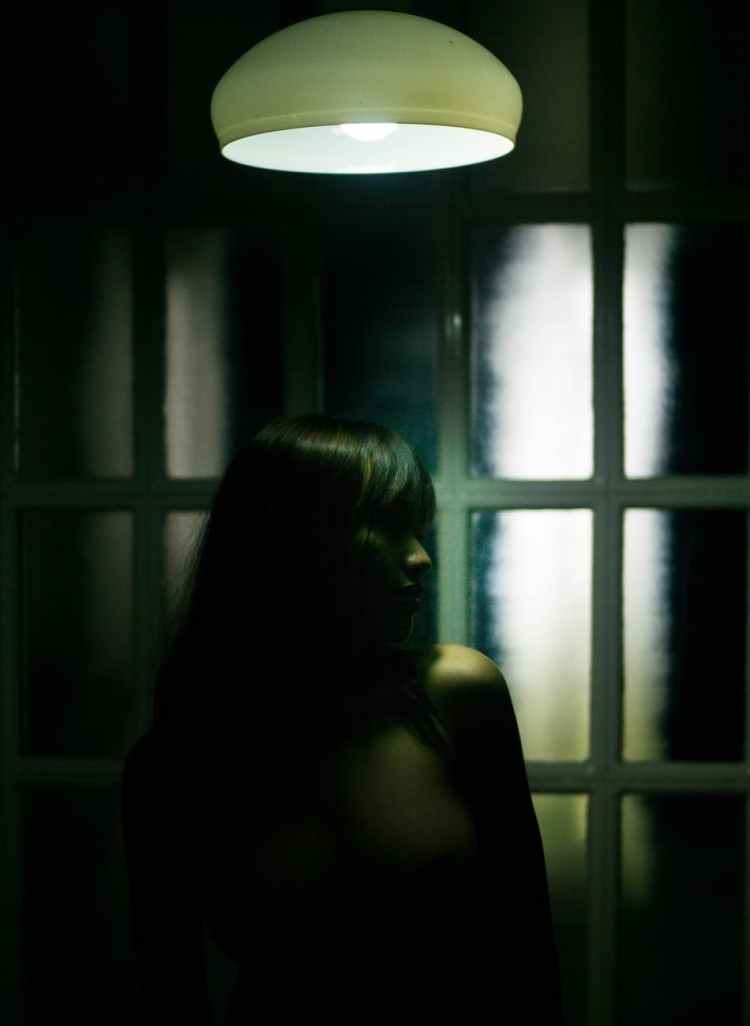 slim woman under electric lamp in dark room