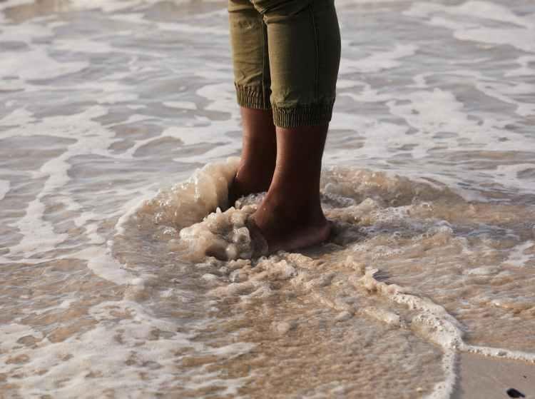 crop black tourist on coast with foamy ocean water