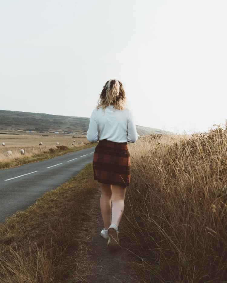 woman standing on empty road in countryside