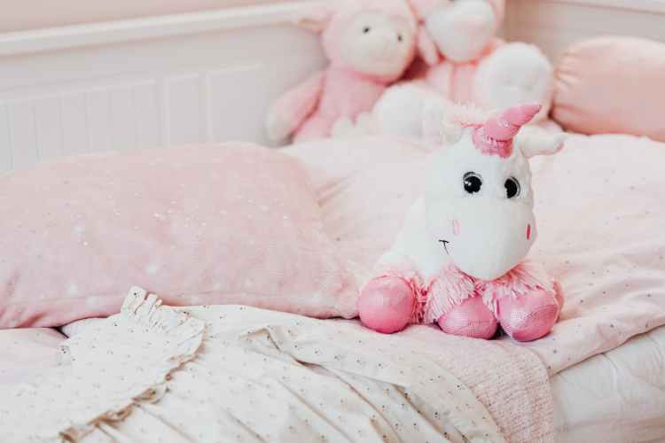 white and pink unicorn plush toy on bed