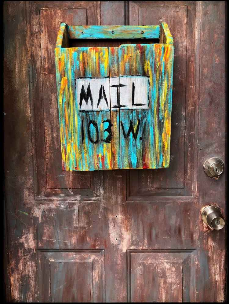 multi coloured wooden mailbox mounted on door