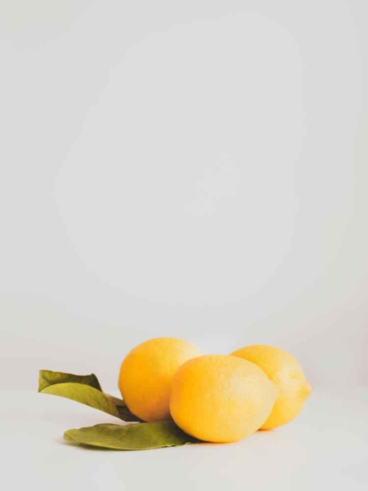 three lemons on white surface