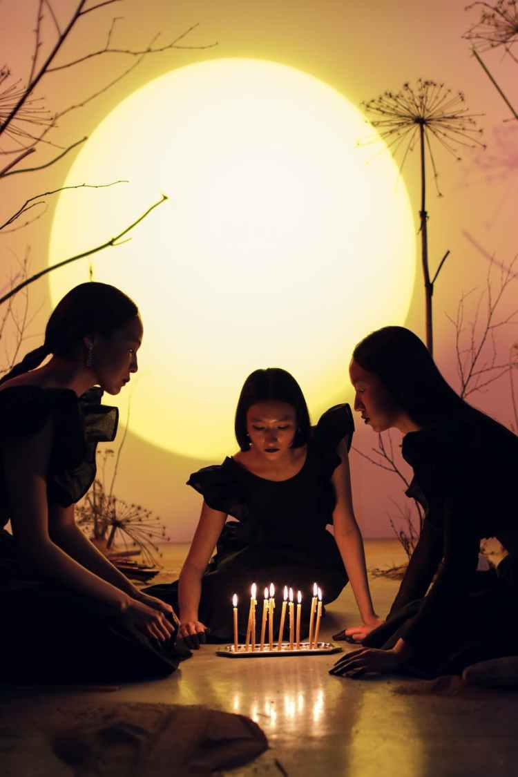 women sitting on the floor while looking at candles