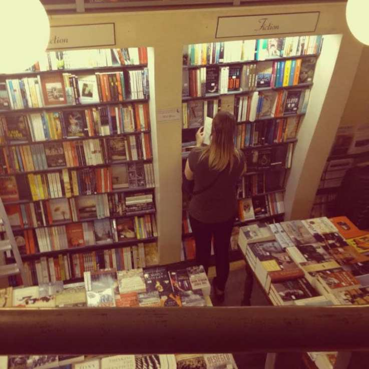 Woman searching for books in a bookstore