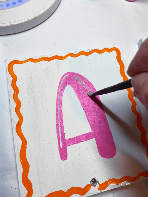 adding glitter paint to letter A