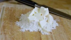 קוצצים שליש מהחמאה עם הקמח על קרש