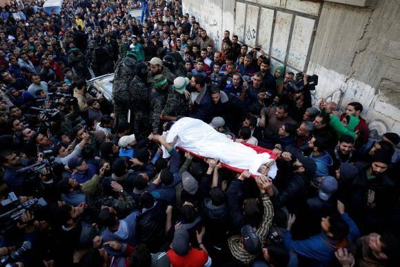 Militantes palestinos do Hamas carregam o corpo de um dos homens mortos em ataque aéreo israelense
