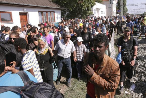 Migrantes que cruzaram fronteira da Sérvia com a Croácia aguardam em campo para fazer registro