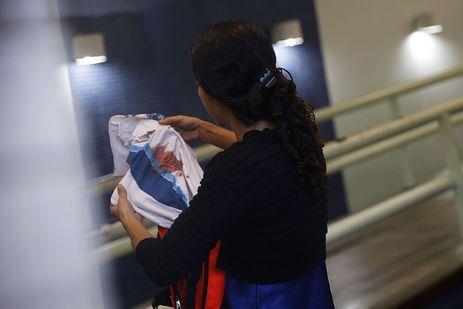 Bruna, mãe do adolescente Marcos Vinicius da Silva, de 14 anos, atingido por uma bala perdida durante operação na favela da Maré, segura camisa da escola que o estudante usava.