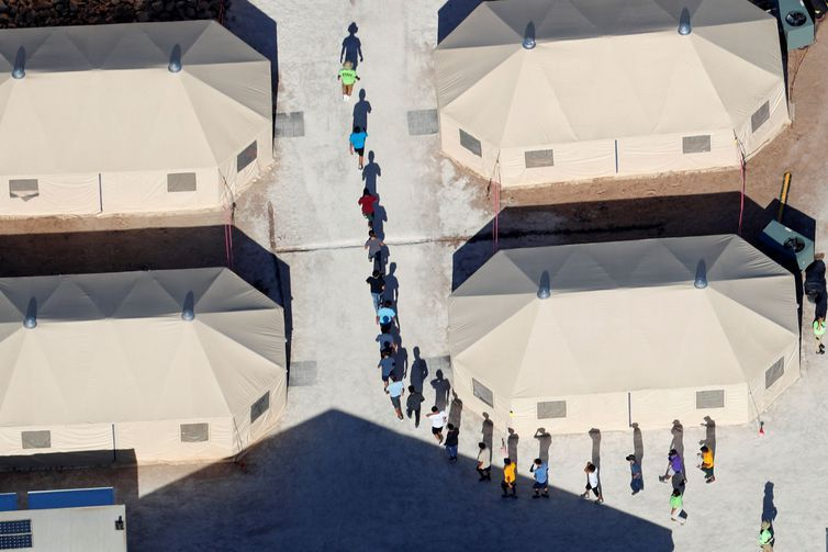 "Immigrant children, many of whom have been separated from their parents under a new ""zero tolerance"" policy by the Trump administration, walk in single file between tents in their compound next to the Mexican border in Tornillo, Texas, U.S. June"