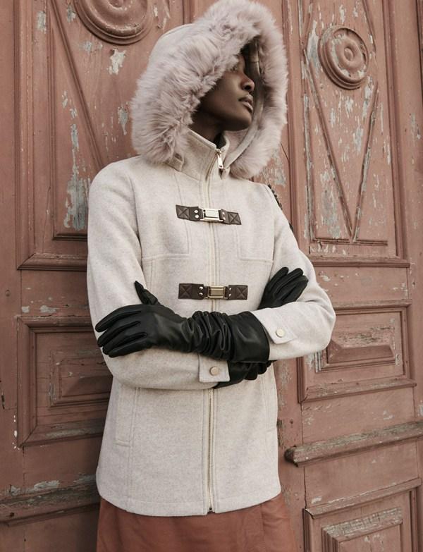 Modelo vestindo casaco de lã batida com detalhes em couro marrom gola de pelo
