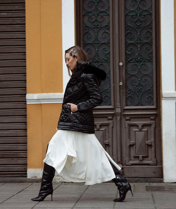 modelo com jaqueta metalizada capuz com pelopreta andando na rua