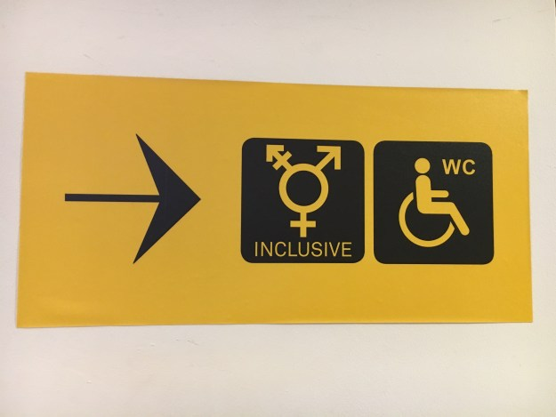 Photo of a sign with an arrow pointing to the right followed by a transgender symbol at the center and disabled toilet sign.
