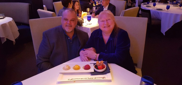 """Ken and Trish, anniversary dinner at Aquaknox. The plate reads """"Happy Anniversary"""" in chocolate frosting."""