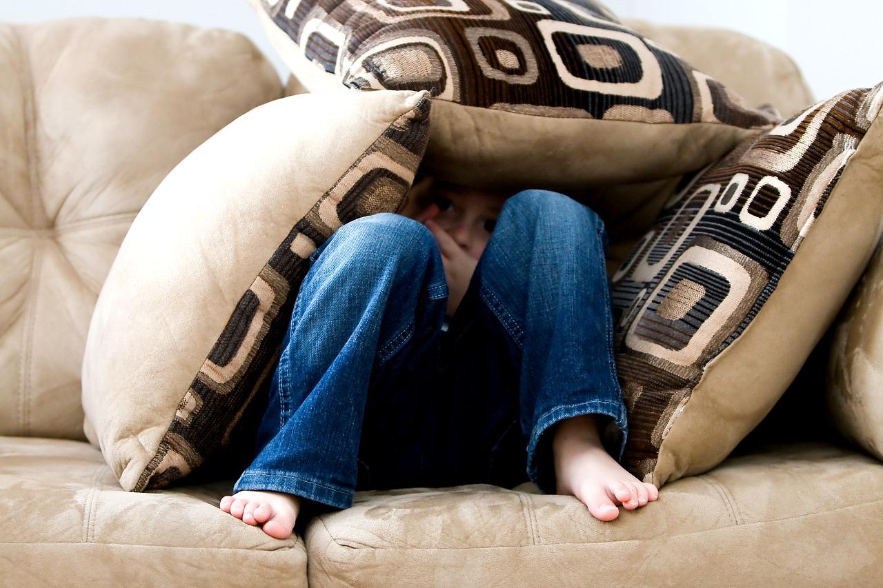 Person hiding under pillows