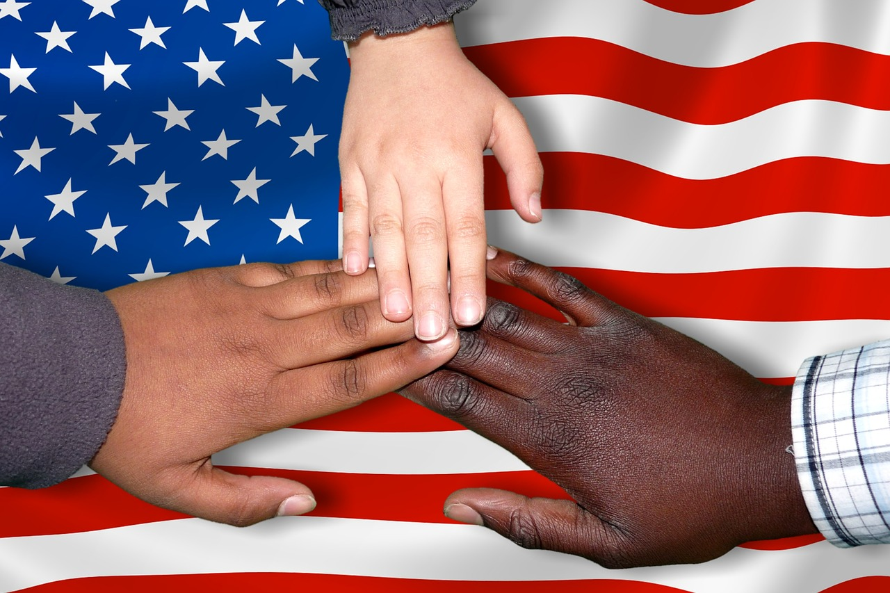 hands joined on American flag representing immigration crisis