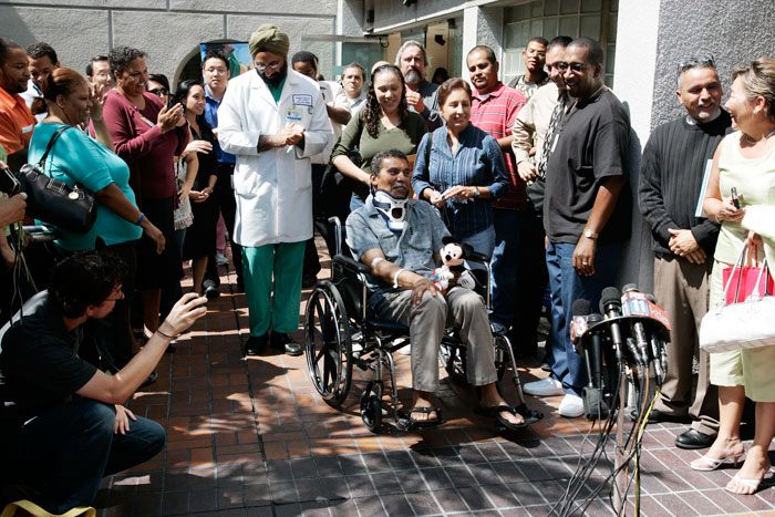 Train crash survivor being wheeled out of hospital surrounded by doctors, people and press.