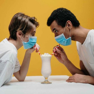Photo of two people sharing a milkshake while wearing masks.
