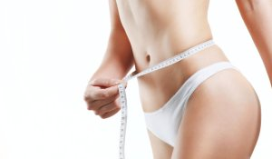 Close up woman body in white underwear with measurement line in hand against white background