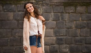 Longhaired hippy-looking young lady in jeans shorts, knitted shawl and white blouse stands near stone wall in old town and smiling