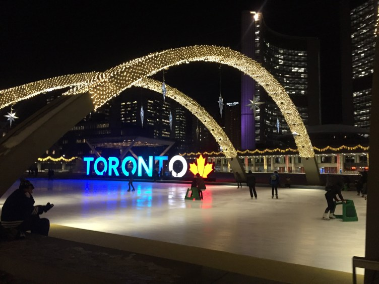 """Nathan Phillips Square had a large ice-rink featuring the arches and the iconic """"Toronto"""" sign, City Hall is in the background."""