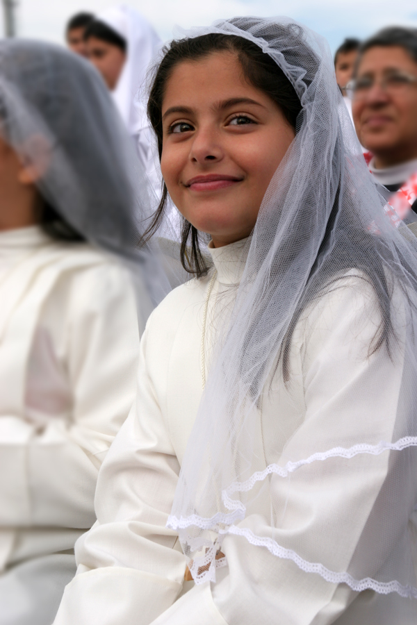 An Iraqi Chaldean Catholic girl awaits her first Holy Communion from Pope Benedict XVI at Amman International Stadium on Sunday, May 10. (Patrick Novecosky photo)