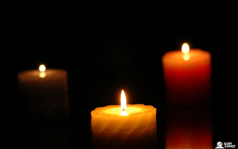 Darkness covering the earth showing three candles in the dark