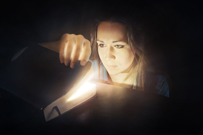 God's will is in the scriptures showing a woman looking at a glowing Bible