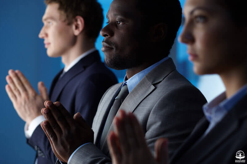 Spirit helps our weaknesses in prayer showing a group of business men praying
