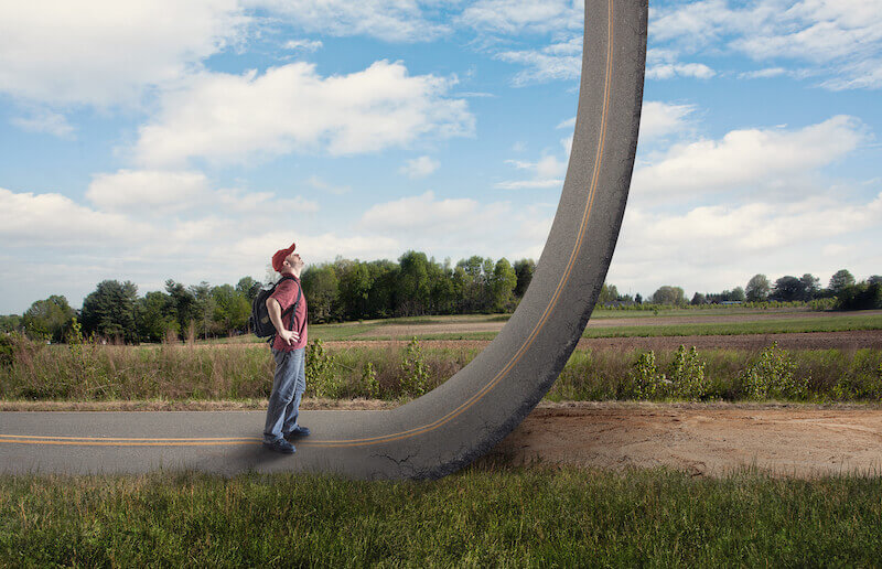 Access with confidence showing a man looking up a road that rises to heaven