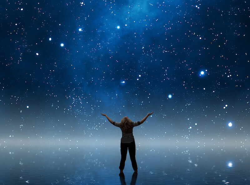 a woman watching the sky with hand lifted up