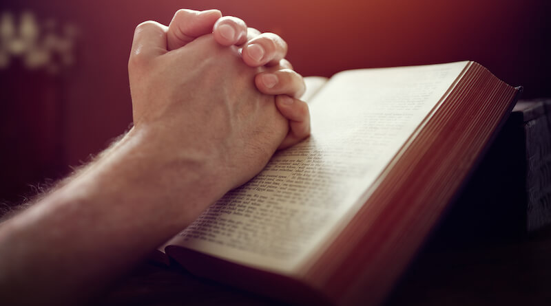 What is a devotional? showing praying hands on the Bible