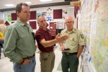 Montana Gov. Steve Bullock, left, listens to Bob Harrington, center, of the Montana State Forest Service discuss the Roaring Lion Fire in Hamilton, Mont. on Aug. 3, 2016. The fire has burned over 7,000 acres of the Bitterroot National Forest. (AP Photo/Patrick Record)