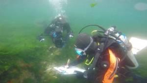 Arqueólogo buzo dibujando la estructura bajo el agua.