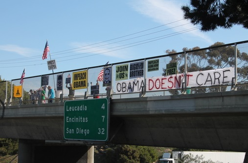 Man On Overpass With Sign