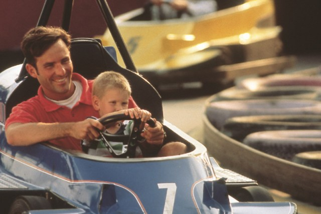 A man and a young child in a go cart in Pigeon Forge.