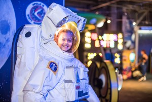 A child wearing a full sized astronaut suit at Wonderworks!