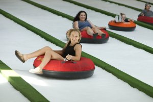 Adults and kids enjoying indoor snow tubing at Pigeon Forge Snow