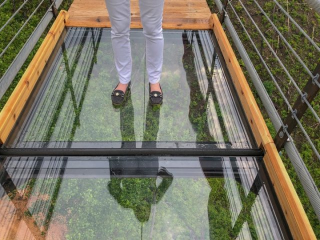 A woman stands on the glass bottom Sky Bridge in Gatlinburg, TN