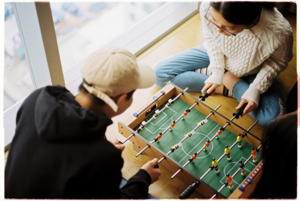 Two people playing foosball on a small table