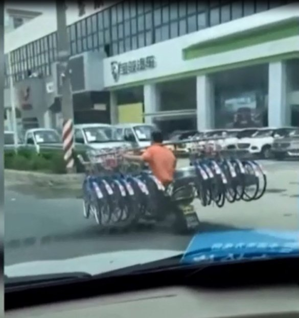 "The man carrying 16 bikes on shoulder while driving motorbike down road causes ""shock"""