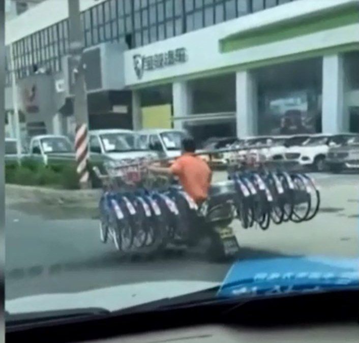 "Video: The man carrying 16 bikes on shoulder while driving motorbike down road causes ""shock"""