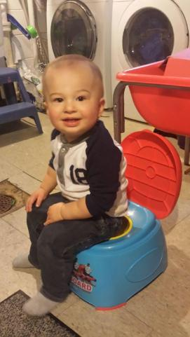 Henry sitting on the potty at daycare at 16 months.