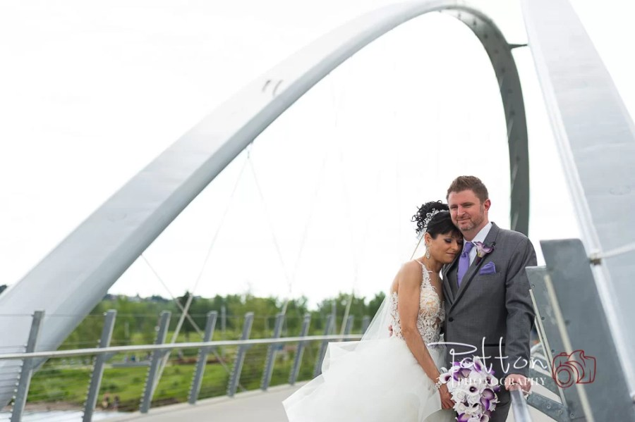 Wedding bride and groom cuddling on bridge